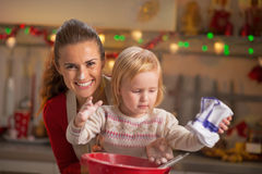 Flour smeared mother and baby making cookies Royalty Free Stock Photo