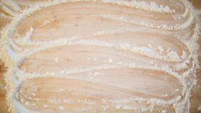 Flour smoothed across a wooden cutting board. In a zig zag pattern Stock Photo