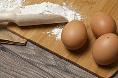 Flour spoon and eggs on wooden table. Royalty Free Stock Photos