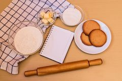 Flour, sugar, butter, empty notebook and prepared cookies Royalty Free Stock Photo