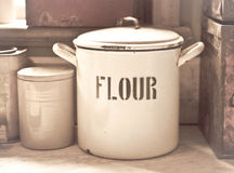 Flour tin. Vintage toned image of an enamel flour tin in an old style kitchen Stock Photo