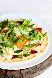 Flour tortilla with fried egg, hummus and fresh mixed salad on a plate. High protein vegetarian tortilla with a filling Royalty Free Stock Photos