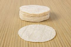 Flour Tortillas On A Bamboo Stitch Background. A pile of flour tortillas with a single in the foreground on a bamboo stitch background stock image