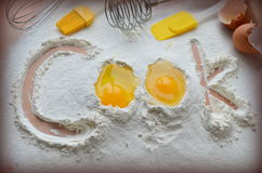 Flour and two eggs. The inscription Cook stock photos