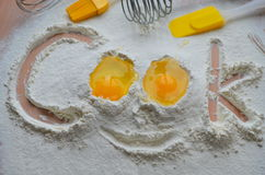 Flour and two eggs. The inscription Cook stock image