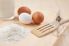 Flour, vidro do leite, whisk e ovos na tabela de madeira Imagem de Stock