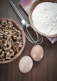 Flour,walnut and eggs on wooden background Stock Photos