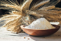 Flour with wheat ears in a wooden bowl on a burlap background. Closeup Royalty Free Stock Photos