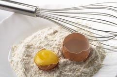 Flour, whisker and egg. Flour pile, egg and metal whisker fragment over gray gradient background stock image