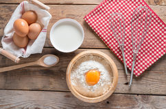 The flour in a wooden bowl, egg, milk and whip for beating. Royalty Free Stock Photos