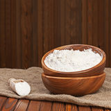 Flour in wooden bowl on nature background. Royalty Free Stock Photos