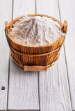 Flour in wooden bucket with handle on old white Stock Images