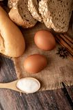 Flour in wooden spoon and eggs on the sack stock photography