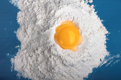 Flour with yolk for preparation of delicious thin captain. On a dark blue cook-table the small group of flour is poured where outpoured yolk of raw egg Royalty Free Stock Images