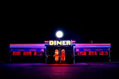 Flourescent American Diner At Night. A traditional American Diner at night with a large sign and clorful luminous, fluourescent and neon lighting that glows in Royalty Free Stock Image