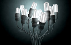 Flourescent Twisted Lights. A collection of regular fluorescent light bulbs with their cords twisted together to create an abstract upward facing being on a dark stock photos