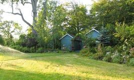 Flourishing farm backyard with sheds and garden house Stock Photo