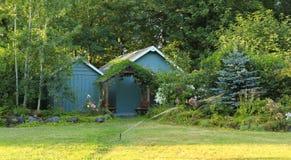 Flourishing farm backyard with sheds and garden house Stock Photos