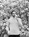 Flourishing and growth. New life and optimism. Spring season concept. Man holding magnolia flower in park with blossoming trees. Macho with beard in yellow royalty free stock images