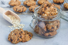Flourless gluten free peanut butter, oatmeal and chocolate chips cookies in glass jar and on table, horizontal Stock Photo