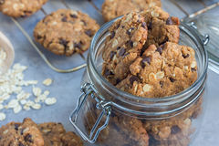 Flourless gluten free peanut butter, oatmeal and chocolate chips cookies in glass jar and on table, horizontal Stock Photos
