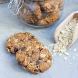 Flourless gluten free peanut butter, oatmeal and chocolate chips cookies in glass jar and on table, square. Format Stock Photos