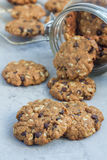 Flourless gluten free peanut butter, oatmeal and chocolate chips cookies in glass jar and on the table, vertical Royalty Free Stock Photo