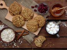 Flourless glutenu bezpłatny masło orzechowe, oatmeal, miód, wysuszeni owoc ciastka i filiżanka kakao z marshmallows na drewnianym Zdjęcie Stock