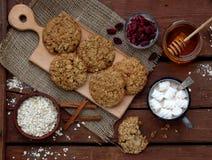 Flourless glutenu bezpłatny masło orzechowe, oatmeal, miód, wysuszeni owoc ciastka i filiżanka kakao z marshmallows na drewnianym Zdjęcia Stock