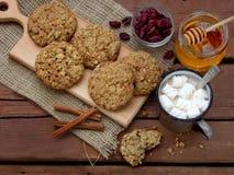 Flourless glutenu bezpłatny masło orzechowe, oatmeal, miód, wysuszeni owoc ciastka i filiżanka kakao z marshmallows na drewnianym Obrazy Royalty Free