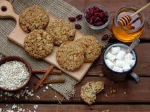 Flourless glutenu bezpłatny masło orzechowe, oatmeal, miód, wysuszeni owoc ciastka i filiżanka kakao z marshmallows na drewnianym Fotografia Stock