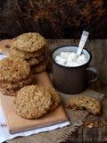 Flourless glutenu bezpłatny masło orzechowe, oatmeal, wysuszeni owoc ciastka i filiżanka kakao z marshmallows na drewnianym tle,  Fotografia Royalty Free