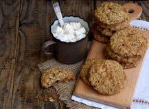Flourless glutenu bezpłatny masło orzechowe, oatmeal, wysuszeni owoc ciastka i filiżanka kakao z marshmallows na drewnianym tle,  Zdjęcia Royalty Free