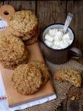 Flourless glutenu bezpłatny masło orzechowe, oatmeal, wysuszeni owoc ciastka i filiżanka kakao z marshmallows na drewnianym tle,  Zdjęcie Stock