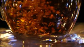Flow of black tea being poured into cup. Slow motion stock footage