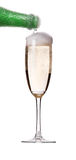 Flow of champagne from bottle into the glass. Glass of champagne on white background. Flow of champange from the top stock image
