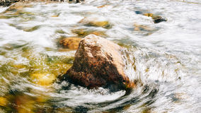 The flow of clear pure water surrounds the stone Stock Photos
