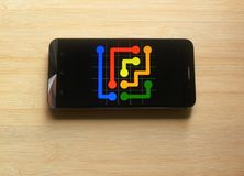 Flow Free game app. On smartphone kept on wooden table stock image