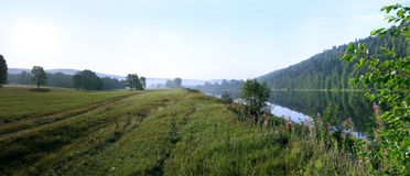 The flow of the river along the quiet green field Royalty Free Stock Image