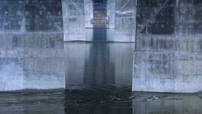 The flow of the river under the bridge, the industrial bridge of concrete supports. 4k video stock footage