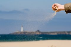 The flow of sand. Sand pouring on the wind on an ocean beach with lighthouse in background Stock Photo