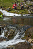 Flow of transparent pure mountain creek water and people on background Royalty Free Stock Photos