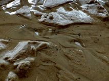 Flow of water over the wet sand stock photos