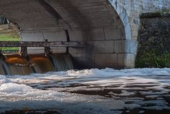 The flow of water under the bridge. Arch of stone bridge, shore and water foam Stock Photos