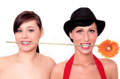 Flower 2 women. Two girls with flower in mouth royalty free stock photos