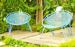 Flower. Blue lawn chairs in the summer garden Royalty Free Stock Images