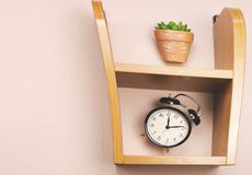 Flower alarm clock jumping on a wooden shelf. Stock Images