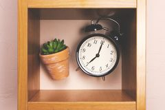 Flower alarm clock jumping on a wooden shelf. Royalty Free Stock Photos