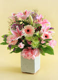 Flower arrangement. In pink on a pastel yellow background royalty free stock image
