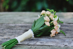 Flower Arrangement. Bridal bouquet of roses on a wood table Royalty Free Stock Images